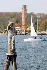 Blick über die Trave in Travemünde zum alten Leuchtturm - Fiete der letzte Seemann auf einer Holzdalbe, gearbeitet aus einem 100 Jahre alten Eichenstamm - Bildhauer Claus Görtz.