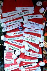 Verkaufsstand mit Weihnachtmützen auf dem Weihnachtsmarkt Santa Pauli / Hamburger Spielbudenplatz; Aufschriften Blasi Hasi, Miststück - Zimtzicke.
