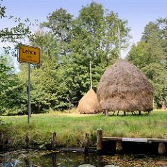 Ortsschild am Wasser - Spreekanal, Fliess / Lehde - Ledy, Stadt Lübbenau; Bootssteg und Heuschober auf der Wiese.