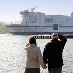 Zwei Touristen stehen im Travemünder Fischereihafen und beobachten das Fährschiff  Nils Holgersson bei der Fahrt auf der Untertrave Richtung Ostsee.