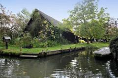 Traditionelles, typisches Holzwohnhaus mit Bootsanlegestelle in Lübbenau - Postkasten am Wasser, ein Hundliegt auf der Wiese und passt auf.