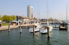 Promenade an der Trave in Travemünde - Segelboote am Steg; im Hintergrund der alte Leuchtturm und das Maritim Hotel