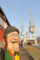 Holzskulptur und Hafenkräne - Kaianlage auf der Wallhalbinsel / ehem. Hafen der Hansestadt Lübeck.
