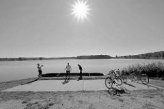 Pause von Fahrradfahrern am See auf der Fahrradroute von Lübben nach Schlepzig - Schwarz-Weiß Fotografie, Gegenlichaufnahme.
