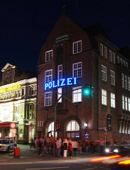 Nachtaufnahme der Backsteinarchitektur von der Davidwache am Spielbudenplatz / Davidstrasse - erleuchteter Schriftzug Polizei; lks. daneben das St. Pauli Theater - Fussgänger warten an der Ampel.
