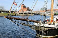 Museumshafen in Lübeck - Bugspriet vom Museumsschiff Johanna; im Hintergrund die historische, denkmalgeschützte Drehbrücke über die Trave, Brückenwärterhaus.