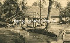 Fussgängerbrücke / Holzbrücke über einen schmalen Fliess im Spreewald - Wohnhaus mit Reet gedeckt.