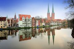 Blick über die Untertrave in Lübeck. Historische Gebäude am Ufer / Uferbebauung - Türme vom Lübecker Dom spiegeln sich im Wasser der Trave.