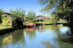 Ferienhäuser, Wochenendhäuser an der Spree in Lübben / Spreewald - Kähne liegen am Flussufer.