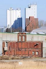 Lagerhaus und Silos auf dem Hafengelände der Hansestadt Lübeck. Reste einer Ziegelfassade  mit Fensteröffnungen.