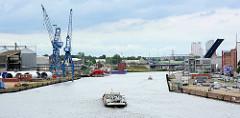 Ein Binnenschiff fährt auf der Trave Richtung Ostsee -  lks. Kräne und Frachtschiffe, re. Speicher und Verwaltungsgebäude an der Lübecker Hafenstrasse - im Hintergrund die hochgeklappte Eric-Warburg-Brücke.