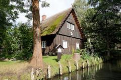 Traditionelles Holzgebäude - altes Wohnhaus mit Reet gedeckt - Fliess in Lübbenau.