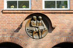 Terrakotta-Dekor am  Schulgebäude in der Torstrasse, Lübeck Travemünde. Junge mit Schiefertafel und Schwamm, Mädchen mit Zopf.