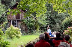 Kahnfahrt mit Touristen durch den Spreewald bei Lübbenau; mit Kletterpflanzen bewachsenes Holzhaus / Schuppen am Ufer.