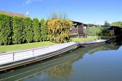 Ufer eines Kanals / Fliess bei Lübben - Aluminiumkähne, Spreekahn aus Metall liegen am Ufer.