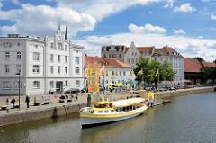 Historische Gebäude an der Untertrave in Lübeck - ein Ausflugsschiff startet zu einer Rundfahrt.