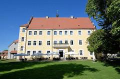 Schlossgebäude in Lübben (Spreewald); Restaurant mit Sonnenschirmen am Oberamtshaus.