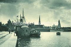 Historisches Panorama vom Lübecker Hafen; ein Küstenschiff liegt am Kai, ein Binnenschiff hat längsseits festgemacht - im Hintergrund die Kirchtürme der Marienkirche und in der Bildmitte der Kirchturm der St. Jacobikirche - lks. der Turm vom Burgt