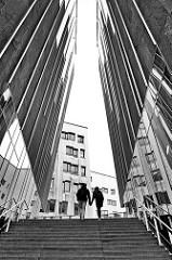 Häuserschlucht mit Treppen - ein Paar geht in der Hafencity Hamburg spazieren - Schwarz Weiß Fotografie.