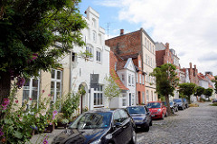 Unterschiedliche Architekturformen - Hausfassaden in der Hansestadt Lübeck - blühende Stockrosen, Kopfsteinpflaster.