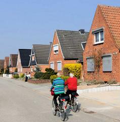 Einzelhäuser mit Satteldach in Lübeck Kücknitz; Radfahrer.