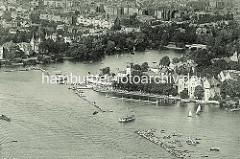 Alte Luftaufnahme vom Uhlenhorster Fährhaus an der Hamburger Aussenalster - die Rennstrecke einer Ruderregatta wird von Booten gesäumt. Im Hintergrund der Lange Zug und Häuser an der Bellevue.