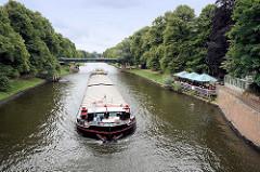 Ein Binnenschiff fährt auf der Lübecker Kanal-Trave - Blick von der Hüxterbrücke.