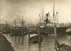 Mit Steinen befestigtes abgeböschtes Ufer im Hamburger Kohlenhafen; die Kohlenladung eines Frachters wird mit einer Kohlenrutsche auf Schuten verladen.