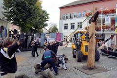 Bildhauersymposium / Spreewaldatelier in Lübbenau; eine Holzskulptur wird auf dem Kirchplatz aufgestellt.