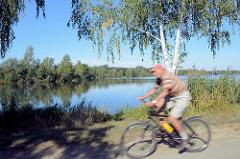Radfahrer auf der Spreewald-Radroute bei Schlepzig - blauer Himmel, Birken am Wasser.
