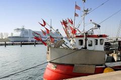 Fischereihafen in Lübeck Travemünde - Kutter am Kai, rote Fahnen am Heck vom Fischkutter - die Wimpel zeigen den Liegeplatz vom Netz oder Grossreuse an - im Hintergrund ein Fährschiff Richtung Ostsee.