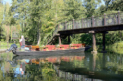 Ein Bootsführer stakt seinen Kahn in Lübben unter einer Holzbrücke hindurch.
