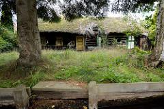 Verfallenes Wohnhaus - das Reetdach hat ein großes Loch; altes Gebäude an einem Fliess in Lübbenau.