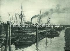 Ufer im Kohlenschiffhafen, Schuten mit Kohlen liegen an den Dalben - weitere Schuten und ein Binnenschiff werden von einem Frachter mit Kohlenrutschen beladen - Qualm steigt aus dem Schornstein des Kohlenfrachters.