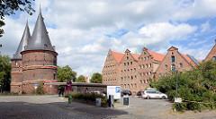 Seitenansicht vom Holstentor, Stadttor zur Altstadt der Hansestadt Lübeck - Strassenansicht der historischen Salzspeicher an der Trave.