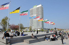 Strandpromenade mit Flaggen, Touristen sitzen in der Sonne - Hotelhochhaus Maritim Travemünde.