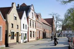 Architektur in Lübeck Travemünde - Wohnhäuser und Schulgebäude - Motorradfahrer / Radfahrer.