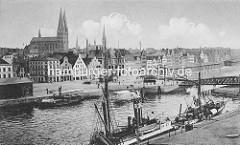 Historisches Panorama der Hansestadt Lübeck - Blick über die Trave; re. die Drehbrücke über die Trave - Lagerschuppen, Frachschiff am Kai - Rauch steigt aus dem Schornstein.