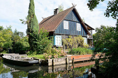 Wohnhaus im Grünen am Wasser - Gebäude mit farbig abgesetzter Holzfassade - Kahn mit Sitzbänken am Ufer.