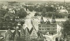 Historischer Blick auf das Lübecker Holstentor und die Salzspeicher an der Trave.