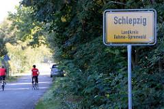 Ortsschild Schlepzig, Landkreis Dahme-Spreewald - im Hintergrund Fahrradfahrer.