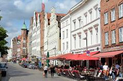 Wohnhäuser / Geschäftshäuser an der Obertrave in Lübeck, Restaurant - Tische und Sonenschirme auf dem Fussweg.