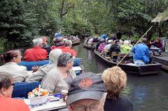 Touristentransport per Kahn in Lübbenau im Spreewald - zwei Kähne haben an einem Kiosk angelegt und lassen sich mit Gurken etc. verköstigen - zwei weitere Boote mit Passagieren fahren vorbei.