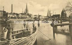 Historische Ansicht vom Lübecker Hafen - eine Frau / Schifferin hängt Wäsche auf; Masten von Segelschiffen, Motorschiff am Kai.