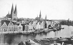Historisches Panorama der Lübecker Altstadt - Blick über die Trave auf die Kaianlage am Ufer - Frachtsegler liegen am Kai; re. das Holstentor - Türme der Marienkirche, Petrikiche und Lübecker Dom.