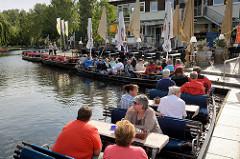 Hafen für Ausflugsboote für Touristen in Lübbenau Spreewald; die Passagiere sitzen auf Bänken an Tischen.