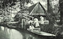 Frauen in Spreewälder Tracht besteigen einen Kahn - Holzhaus mit Reedach.