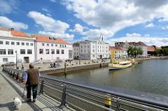 Fussgänger auf der Fussgängerbrücke Obertrave - Blick auf die Promenade an der Trave, historische Architektur der Hansestadt Lübeck.