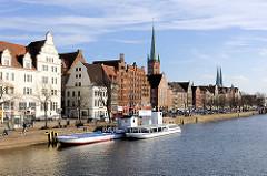 Promenade und Anleger an der Trave in Lübeck; historische Gebäude / Speicher der Lübecker Altestadt - Kirchturm der Petrikirche.