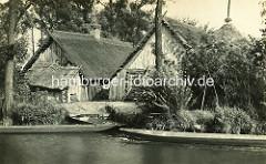 Spreewaldansicht früher - altes Foto von Holzhäusern und Schuppen mit Reet gedeckt; Spitze eines Heuschobers und Spreewaldkähne am Ufer.